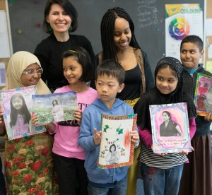 Young students with teachers holding up feminism projects