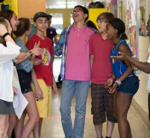 young students standing in school hallway laughing