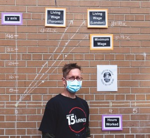 David Stocker standing in front of student project on wall outside of school