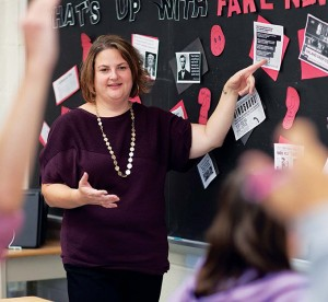 teacher in front of classroom pointing at fake news