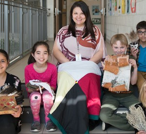teacher and students sitting on stairs displaying indigenous history projects