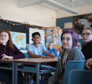 Students sitting at large desks in classroom