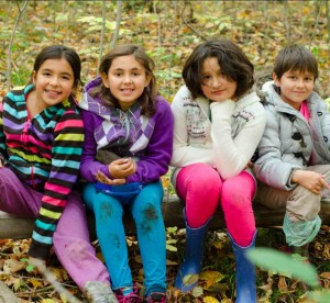 elementary students sitting on log in the woods