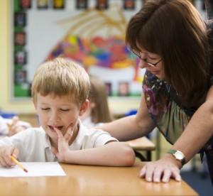 Teacher leaning over elementary student explaining paper in classroom