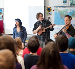 three musicians performing in front of classroom of elementary students