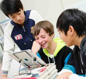 three students looking at tablet propped up on textbooks