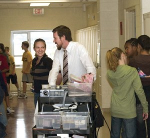 Teacher pushing AV cart through hallways at school