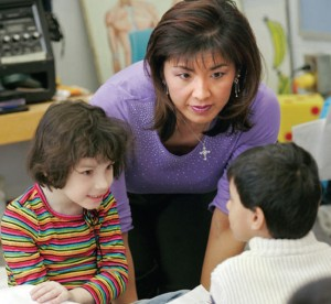 teacher leaning over table talking to two students