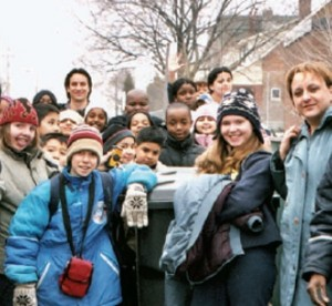Teachers and students in winter clothing posing next to bus