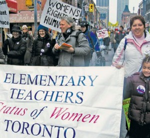 "women etfo members marching down street with picket signs that read ""elementary teachers status of women in toronto"""