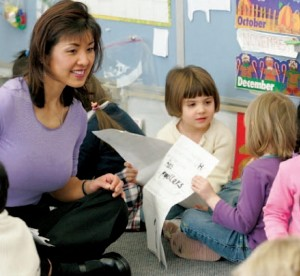 Teacher interacting with kindergarten students who have books