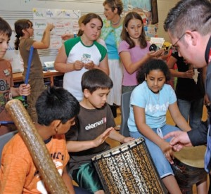 students playing drums and other instruments with teacher conducting them