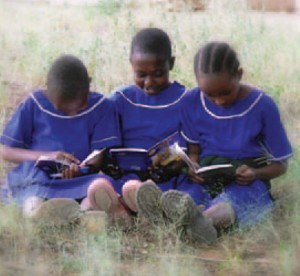 three students sitting in field reading books