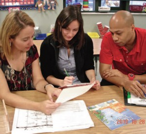 three teachers look at paper