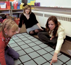 Two teachers working with student on mat divided into squares
