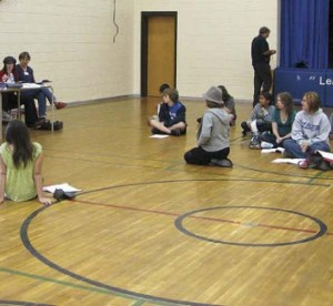 kids sitting on floor in gymnasium