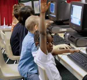 student with hand up and other students in background working on computers in computer lab