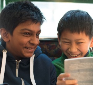 Two elementary students laughing while reading a book
