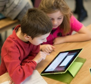Two young students working with tablet