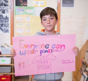 "Male student holding paper that says ""everyone can wear pink"""