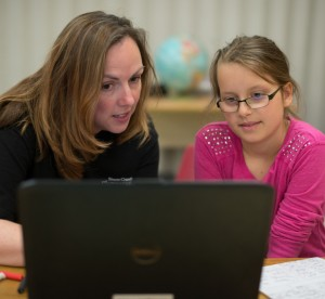 Teacher working with student using a laptop