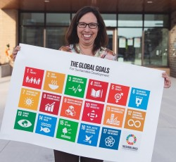 Woman holding poster with The Global Goals for Sustainable Development displayed