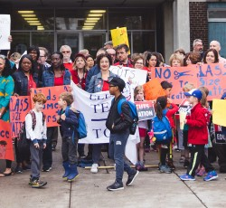 teachers and parents standing in front of school with signs