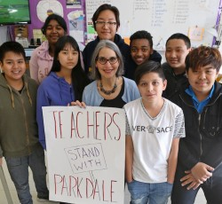 Teacher and students standing in class with political sign. Photo by Cheol Joon Baek