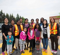 Writer Charmain Brown with students and parent volunteers standing in front of a school