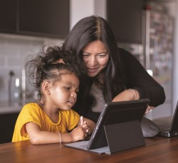 Parent showing child how to use laptop