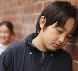 Elementary student leaning against brick wall looking sad or hurt