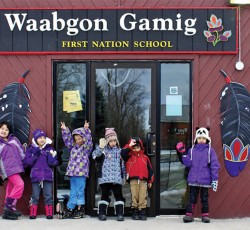 Young children in winter wear standing out front of Waabgon Gamig First Nation School