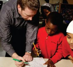 teacher working one on one with student on paper