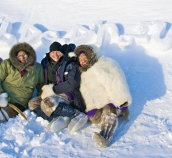 aboriginal women wearing parkas sitting in the snow