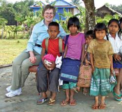 overseas teacher sitting with students outside