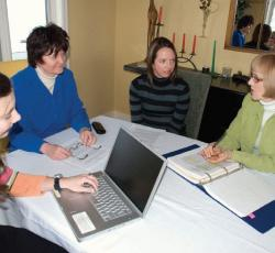 Female teachers sitting around table with open binders and a laptop