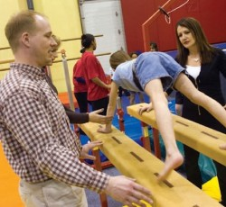 Two teachers teaching young student how to use gymnasium equipment