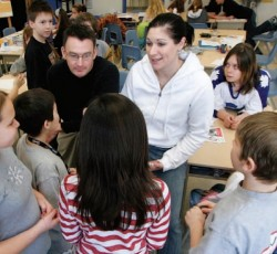 Teacher standing with students providing an explenation