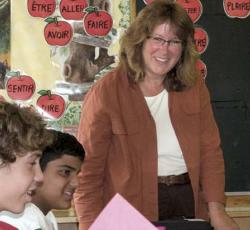 Teacher smiling at front of classroom with three students in foreground