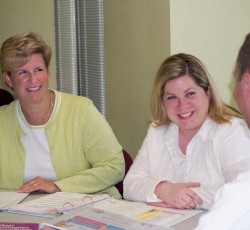 Teachers sitting together smiling at one another