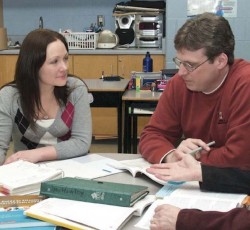 teachers sitting together at table with open textbooks in classroom