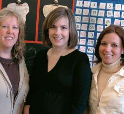 Three woman teachers posing in classroom