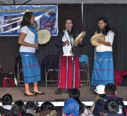 three women performing on stage with drums