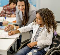 Teacher working with student in wheelchair
