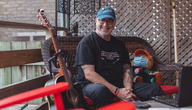 Gordon Nore on patio with guitar
