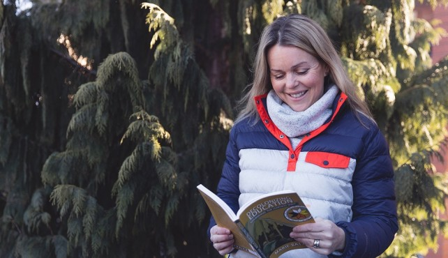 Courtney Morgan standing in front of tree holding book
