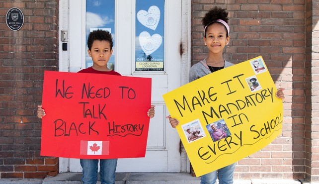 Children standing outside of school holding Black History posters they made