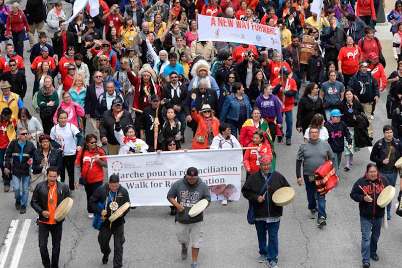 Aboriginal community members marching down street
