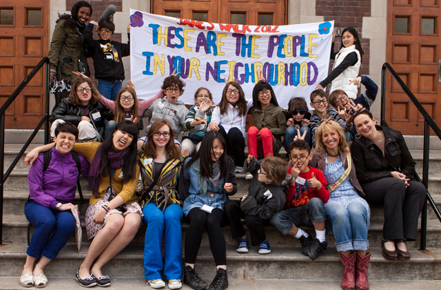 "students sitting together holding sign that reads ""These are people in our neighbourhood"""