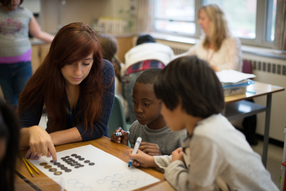 Teacher working with elementary student at table